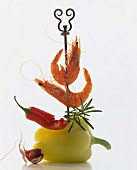 A skewer piercing a pepper, a chilli and whole prawns
