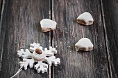 Bell shaped, pfeffernüsse (gingerbread) cookies and a pfeffernuss cookie decorated with an almond on top of a star shaped ornament