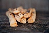 Bread sticks with poppy seeds on a wooden table