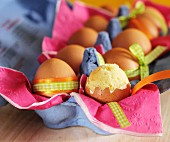 Sponge cake in an eggshell in a full carton of eggs with Easter decorations