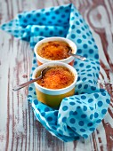 Two little dishes of creme brulee on a polka dot fabric
