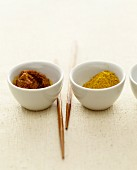 Curry paste and curry powder in small bowls