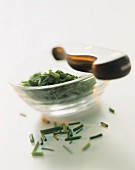 Finely chopped chives in a small glass bowl