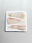 Three monkfish fillets on a white tray