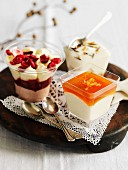 Three different types of puddings on a wooden tray