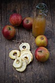 Fresh apples, apple juice and dried apple rings on a wooden table
