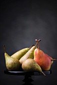 Several pears on a cake stand