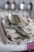 Silver spoons on top of a stacked linen dish towels
