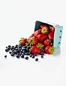 Fresh Strawberries and Blueberries Spilling from a Carton
