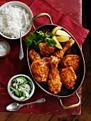 Würzige Hähnchenkeulen mit Reisbeilage und Gurkensalat