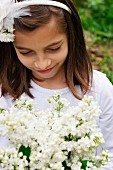 A girl with a bunch of white lilacs in the garden