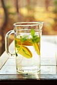 Limonade mit Zitronenscheiben und Minze im Glaskrug