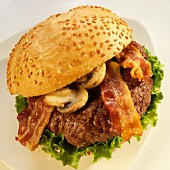 Hamburger with Bacon, Mushrooms and Lettuce on a Sesame Seed Bun