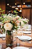 Rosenstrauss auf einer rustikalen Hochzeitstafel im Frühling