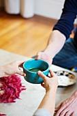 Hands serving Matcha tea