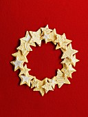 Wreath made of star cookies in front of a red background