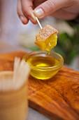 Brotwürfel wird in Olivenöl getaucht