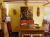 A dining room in a country house with a wooden table and Asian pieces of art