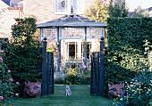 Katze und Katzenfiguren am Gartentor vor einem englischen Landhaus mit Gartenpavillon