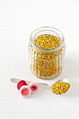 Flower pollen in a small jar and on a spoon