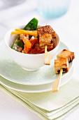 Tofu satay skewers on a bed of vegetables