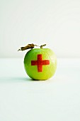 An apple with a red cross