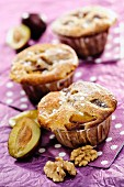 Plum and Walnut Muffins on purple background, selective focus