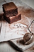 Three brownies dusted with cocoa on a white scrap of paper with the words Eat Me