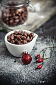 Caramelised almonds in a white bowl with Christmas decoration