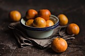 Clementines and enamel bowls on a wooden surface