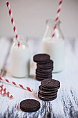 Stacks of Oreo cookies with bottles of milk and drinking straws on a wooden plate