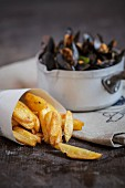 Steamed mussels in a saucepan and chips in a paper cone