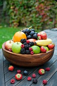 A large wooden bowl filled with fresh fruit and berries