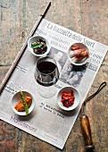 Assorted antipasti and a glass of red wine on a newspaper (Italy)