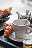 Croissant, coffee and honey for breakfast