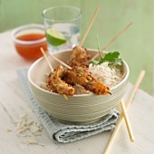 Chicken satay skewers on a bed of rice