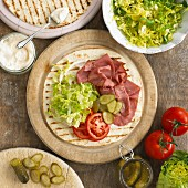 A wrap with pastrami, salad, pickled gherkins, mayonnaise and tomatoes