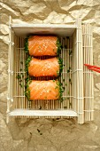 Salmon sushi in a basket made from bamboo mats