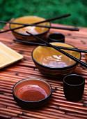 Asiatisches Essgeschirr mit Stäbchen auf Bambusmatte
