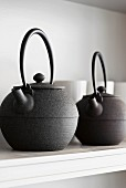 Two teapots on a shelf on the wall