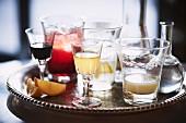 Verschiedene Drinks in Vintage-Gläsern auf Silbertablett