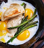 Fried eggs with asparagus and ravioli