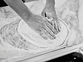 Hands brushing flour over pizza dough