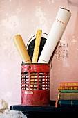 Alter, roter Metallbehälter mit Papierrollen und Lineal neben Bücherstapel auf Konsole an Wand mit abblätternder Farbe