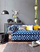 Blau-weiß gepunktetes Polstersofa vor grauer Wand mit Ablagetisch und gelber Macrameé-Blumenampel