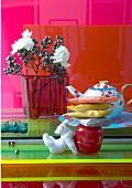 Buntes Stillleben mit roter Aalto Glasvase und edler Teekanne auf verschiedenen farbigen Glasplatten arrangiert