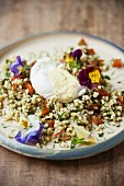 Bulgur salad with a poached egg and edible flowers