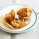 Apple and walnut muffins in baking parchment on a plate
