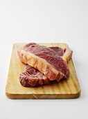 Two beef steaks on chopping board