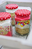 Cupcakes with frosting and sugar sprinkles in jars